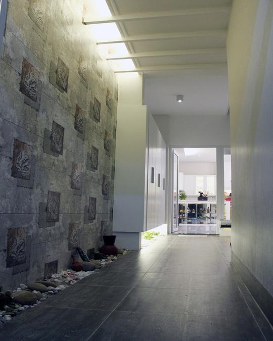 Phòng khách, khu sinh hoạt chung được làm ở giữa nhà. Hành lang dẫn tới khu vực này được trang trí bởi một khoảng dọc sỏi đá.