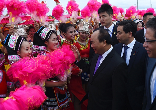 Thủ tướng Nguyễn Xuân Phúc chào các sinh viên Trung Quốc ra đón đoàn tại sân bay - Ảnh: VGP/Quang Hiếu