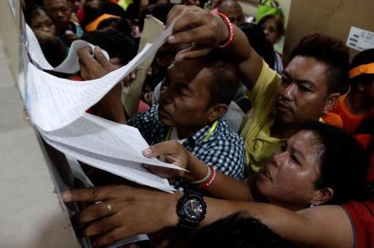 Cử tri tìm tên mình trong danh sách cử tri tại một điểm bỏ phiếu ở TP Tondo hôm 9-5. Ảnh: Reuters