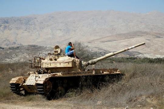Một người đàn ông ngồi trên chiếc xe tăng cũ bên phía biên giới Israel giữa nước này với cao nguyên Golan, để theo dõi giao tranh ở Syria. Ảnh: Reuters