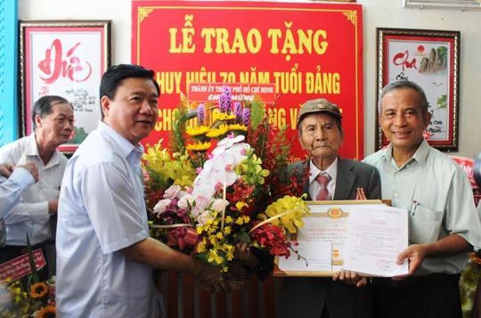 Ủy viên Bộ Chính trị, Bí thư Thành ủy TP HCM Đinh La Thăng tặng hoa cho ông Đặng Văn Hạt