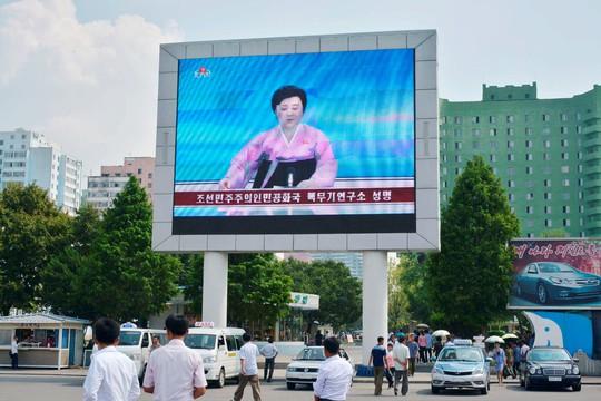 Người dân Triều Tiên đi ngang một màn hình lớn phát thông báo của chính phủ về vụ thử hạt nhân thứ 5 tại Bình Nhưỡng hôm 9-9. Ảnh: Reuters