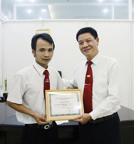 Ông Trương Đình Quý (bìa phải), Phó Tổng giám đốc Vinasun, trao giấy khen và tiền thưởng cho tài xế Đồng Văn Long