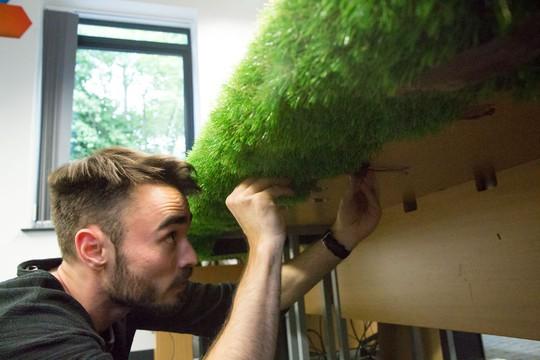 Cẩn thận nẹp lại từng góc bàn để cỏ nhân tạo trùm kín tránh bị lộ là cỏ giả.