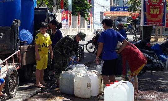 Các chiến sĩ thuộc Huyện đội Kiên Hải đang đưa nước vào các can nhựa để phân chia cho dân.