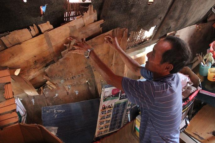 Ông Võ Văn Sơn (61 tuổi, ngụ kênh Tẻ, phường Tan Kiểng, quận 7) đang cơi nơi lại căn chòi của mình sau đợt mưa. Hiện  nơi ở của ông có khả năng sập bất cứ lúc nào.