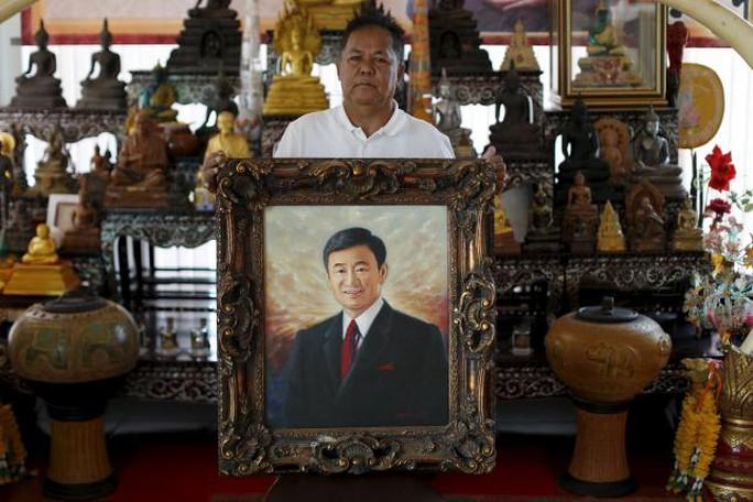"""Thủ lĩnh """"áo đỏ"""" Kwanchai Praipana cầm ảnh ông Thaksin ở văn phòng tỉnh Udon Thani ngày 15-9.  Ảnh: Reuters"""
