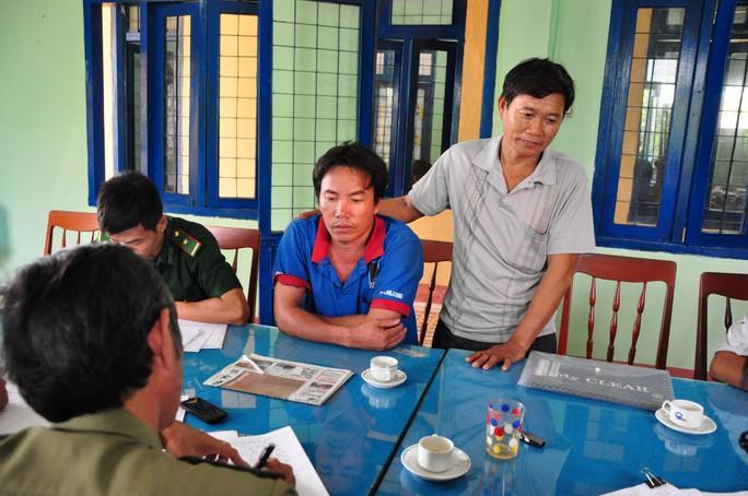 Ngư dân Đặng Dũng (ngồi) cùng ngư dân Lê Khởi (đứng) làm việc với lực lượng chức năng Quảng Ngãi