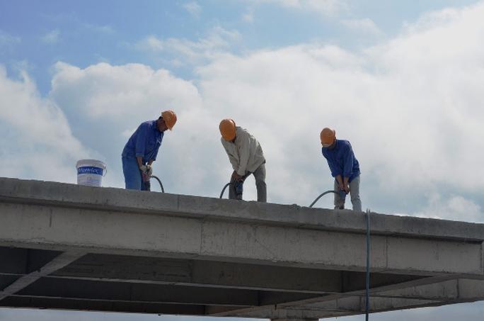 Công nhân dùng máy khoan phá bê tông phá dỡ tầng tum