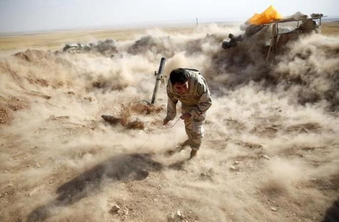 Một chiến binh người Kurd bắn đạn cối về phía Zummar, khu vực IS kiểm soát gần TP Mosul. Ảnh: Reuters