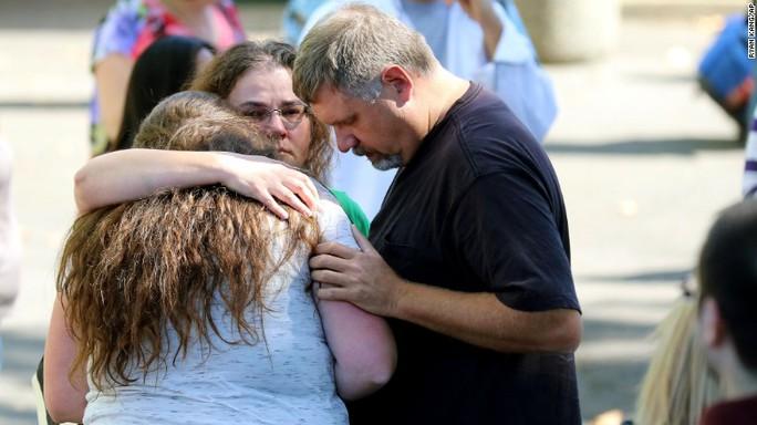 Sinh viên đoàn tụ với người thân sau khi trải qua vụ nổ súng kinh hoàng. Ảnh: AP