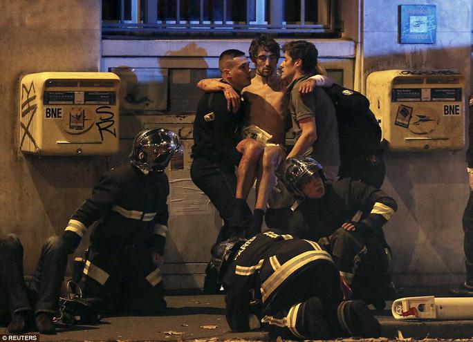 Cảnh sát trợ giúp một nạn nhân trong vụ khủng bố tại nhà hát. Ảnh: Reuters