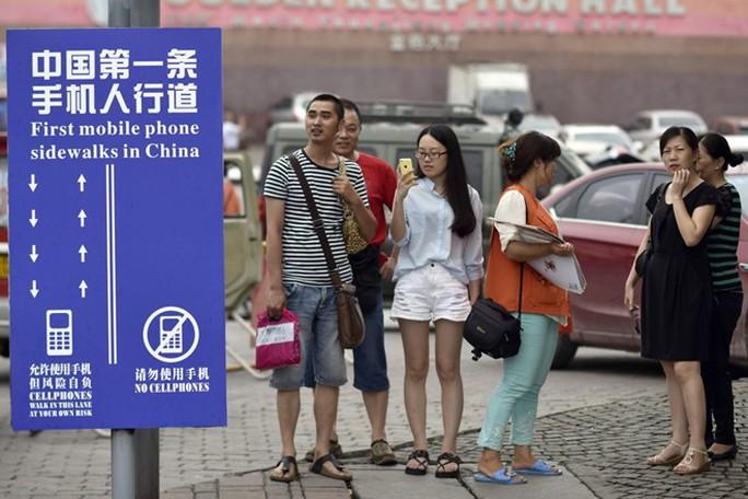 Một làn đường dành riêng cho những người vừa đi bộ dán mắt vào smartphone ở Trùng Khánh, Trung Quốc. Ảnh: TWP.