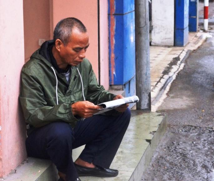 Mưa rét không có khách, một bác lái xe ôm trên đường Tôn Đức Thắng ngồi tranh thủ đọc báo