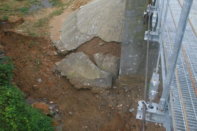 Không chỉ trên cầu, thành móng sát chân cầu cũng bị nứt toạc ra kéo theo những mảng tường bê tông ta luy bị đổ xuống mép hố