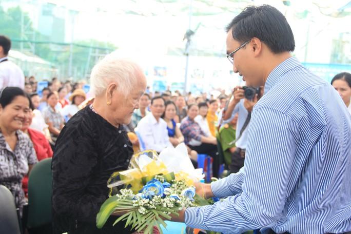 Ông Bùi Gia Hiếu, Hiệu trưởng Trường THPT Nhân Việt, tặng hoa  cho mẹ Việt Nam anh hùng Trần Thị Cách Ảnh: ĐẶNG TRINH
