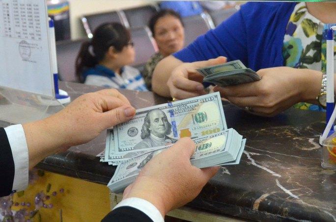 Giao dịch USD tại một ngân hàng ở TP HCM ngày 18-12 Ảnh: TẤN THẠNH
