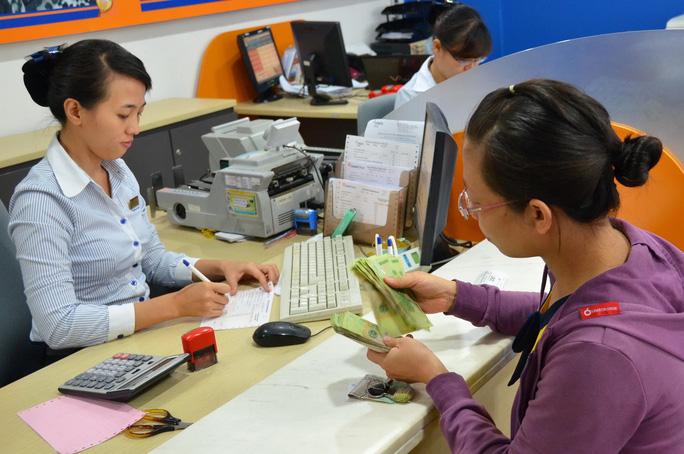 Lạm phát giảm nhưng lãi suất cho vay vẫn ở mức cao, đẩy doanh nghiệp vào thế khó. Trong ảnh: Khách hàng giao dịch tại Ngân hàng Đông Á Ảnh: TẤN THẠNH
