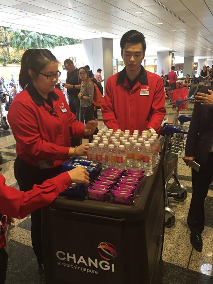 Hảnh khách chuyến bay SQ001 của hãng Singapore Airlines được cấp đồ ăn nhẹ và thức uống. Ảnh: CNA