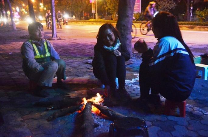 Người lao động tranh thủ lúc nghỉ ngơi ngồi quanh bếp lửa để sưởi ấm cùng các em học sinh
