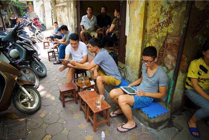 Người Việt dùng smartphone, tablet để lên mạng tại một quán cà phê vỉa hè Hà Nội. Ảnh: CNET.
