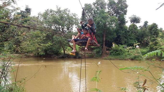 Hàng ngày hàng trăm lượt người, có cả trẻ em đu cáp treo qua suối