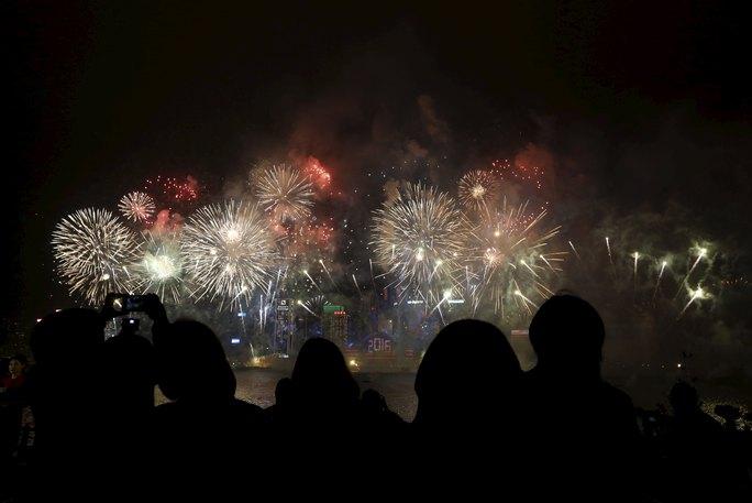 Người dân Hồng Kông xem pháo hoa bắn trên Cảng Victoria. Ảnh: Reuters