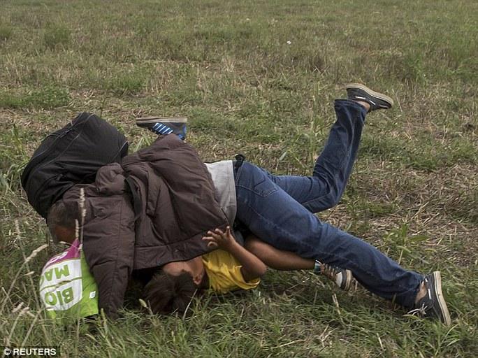 Cả hai ngã nhào khi bị nữ quay phim ngáng chân. Ảnh: Reuters