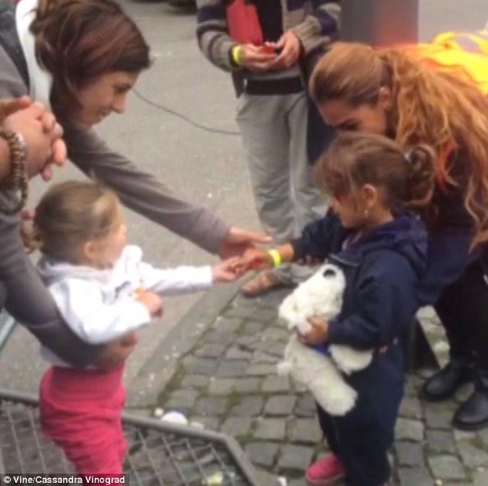 Bé gái người Đức chia bánh cho bé gái nhập cư. Ảnh: Vine