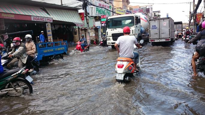 Mưa ngập khiến các phương tiện lưu thông hết sức khó khăn, nhiều khu vực ngập sâu hơn 0,5m, lút bánh xe máy và kéo dài gần 300m