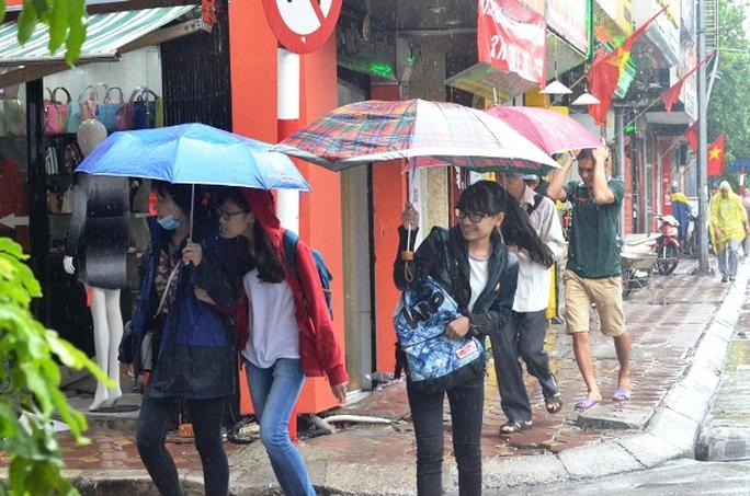 Nhiệt độ xuống thấp khiến diện mạo con người Hà Nội cũng thay đổi. Áo khoác, áo len và kèm theo cả áo mưa thay cho áo cộc tay vào ngày hôm qua