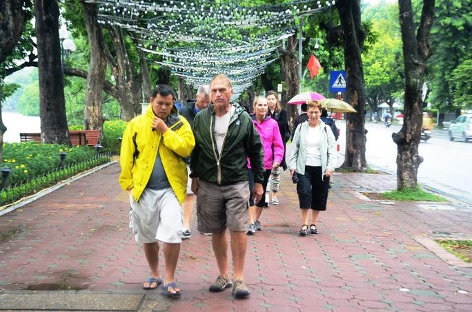 Du khách nước ngoài dạo phố quanh Hồ Gươm với áo khoác gió