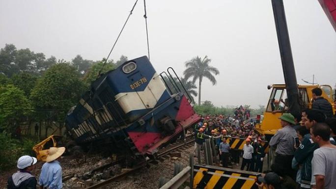Một xe cẩu đang nỗ lực giải cứu đầu máy tàu hỏa ra khỏi hiện trường
