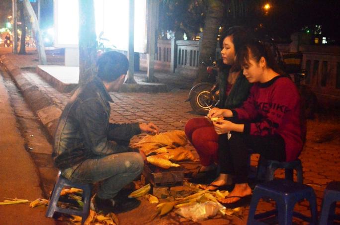 Mùa đông tại Hà Nội, món ngô nướng ven đường được rất nhiều bạn trẻ ưa chuộng vì vừa được thưởng thức những bắp ngô nướng thơm lừng nóng hổi vừa được ngồi sưởi ấm quanh bếp than hồng