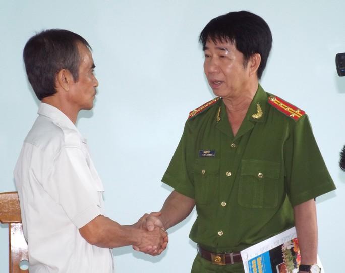 Đại tá Phạm Thật, Phó Giám đốc Công an tỉnh Bình Thuận, bắt tay ông Huỳnh Văn Nén sau khi trao quyết định đình chỉ điều tra Ảnh: MINH QUÂN