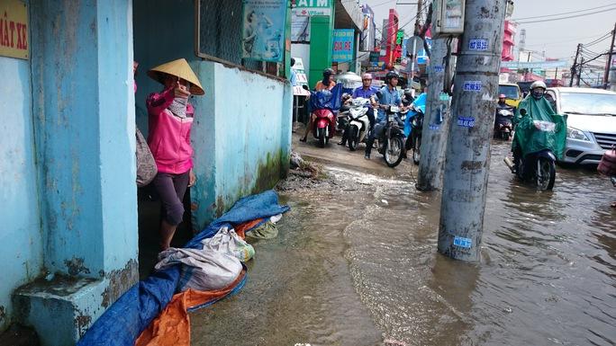 Một gia đình phải lấy bạt che chắn để ngăn nước tràn vào nhà