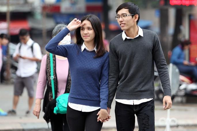 Đôi bạn trẻ dắt tay nhau dạo phố trong thời tiết se lạnh của Sài Gòn