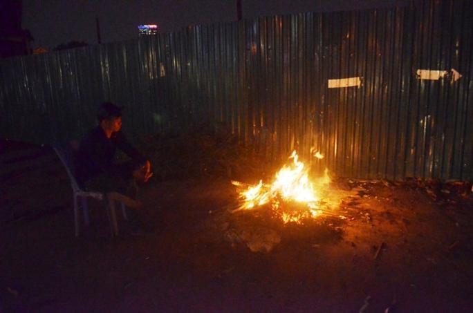 Một bảo vệ công trường tại dốc Bưởi đốt củi sưởi ấm giữa đêm lạnh
