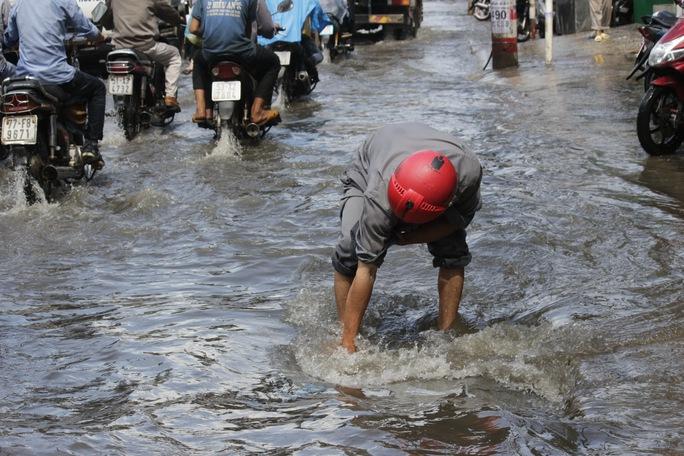 Một người dân đang túc trực tại một ống cống để khơi thông dòng nước và nhắc nhở người đi đường