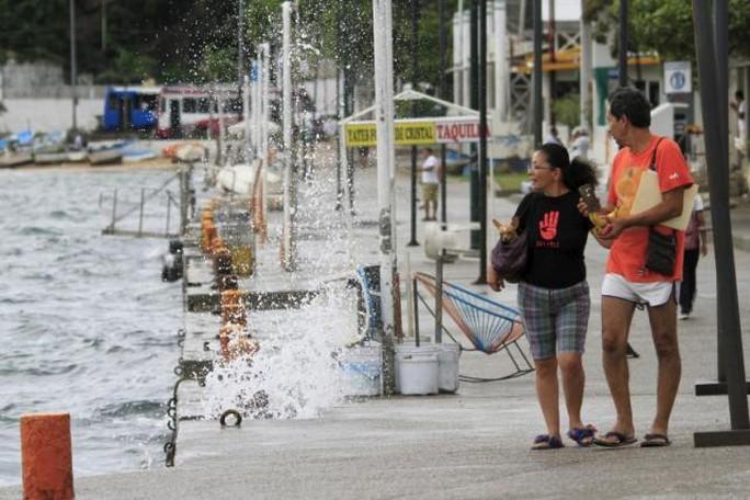 Du khách nhìn sóng vỗ vào bờ biển TP Acapulco khi bão đang đổ bộ. Ảnh: Reuters