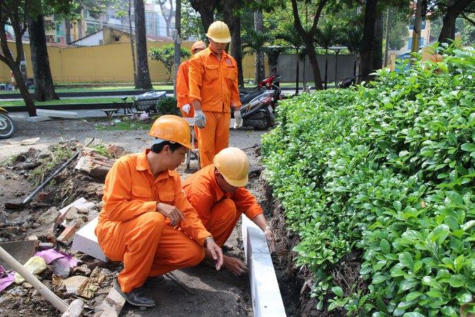 Anh Tạ Văn Trung - tổ trưởng tổ sản xuất Công ty Dịch vụ công ích quận 5, TP HCM (hàng đầu, bìa trái) - hướng dẫn đồng nghiệp chăm sóc cây cảnh