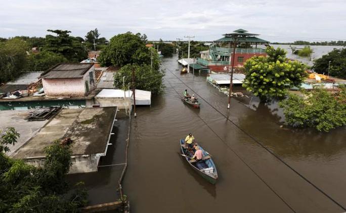 Người dân Asuncion dùng thuyền đi lại trong nước lũ. Ảnh: Reuters