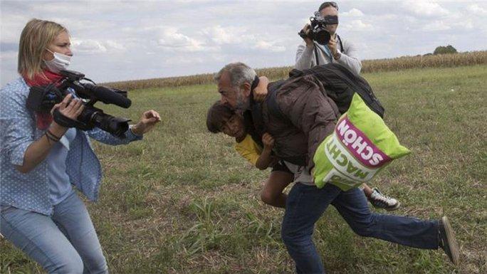 Ông Osama Abdul Mohsen bế con trai Zaid chạy trốn cảnh sát. Ảnh: Reuters