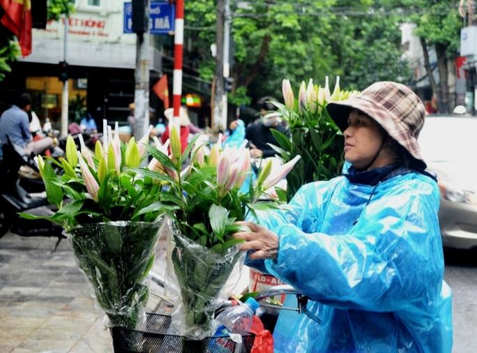 Người phụ nữ bán hoa dạo dậy từ sớm đi lấy hàng rồi đưa hoa tươi đi bán dọc phố trong mưa