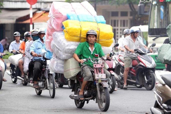 Nhiều xe chở hàng hóa cồng kềnh cao gấp đôi người ngồi