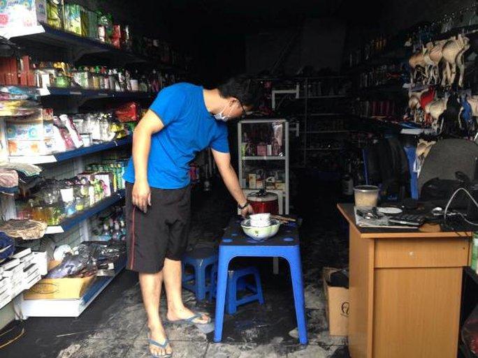 Anh Tô Kim Tuấn (32 tuổi, chủ cửa hàng bán tạp hóa tại tầng 1 tòa nhà CT4A) đang thu dọn cửa hàng tạp hóa đen kít do bị ám khói.