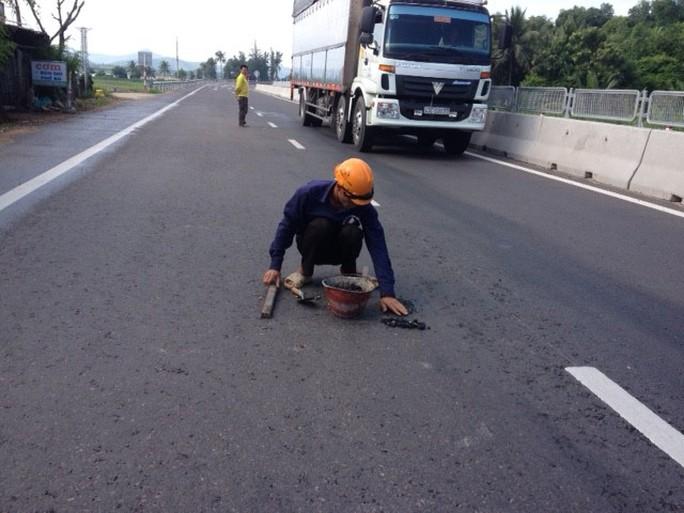 Công nhân dùng tay và cây nhỏ đập đập lên mặt bê tông để lấp ổ gà tại Gành Đỏ, thị xã Sông Cầu (tỉnh Phú Yên)