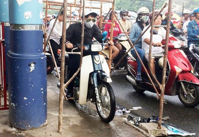 Nhiều người đi xe máy sợ trễ giờ làm nên đã chui dưới giàn giáo đang sửa chữa biển hiệu cổng KCN Tân Bình trên đường Tây Thạnh để thoát khỏi cảnh kẹt xe.