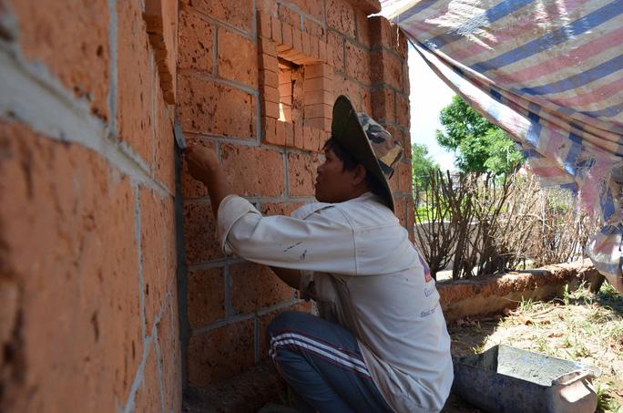 Thợ xây đang tô lại bức tường bọc bên ngoài khu lưu niệm xây bằng đá tổ ong