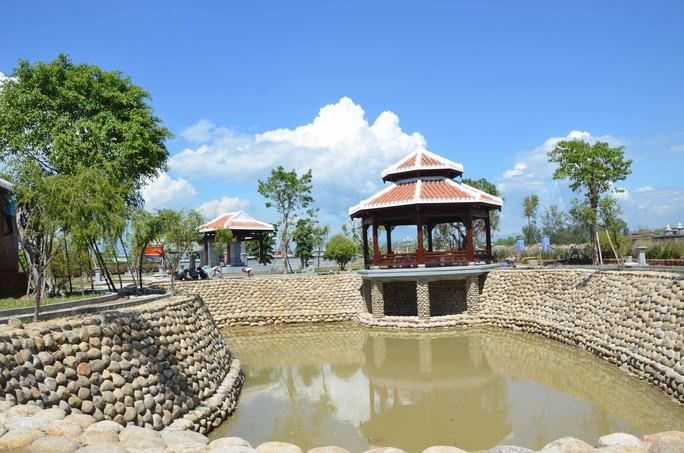 Bên cạnh phần mộ của ông Thanh là hồ nước với cây cối và thảm cỏ xung quanh